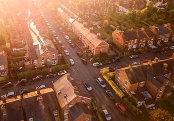 An aerial view of a crossroads showing multiple houses in the street