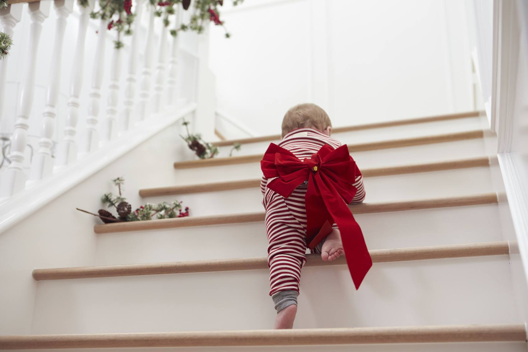 Baby crawling up staircase with bow