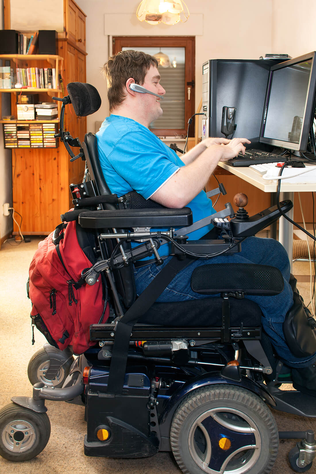 Gentleman with cerebral palsy in electric wheelchair user using a computer